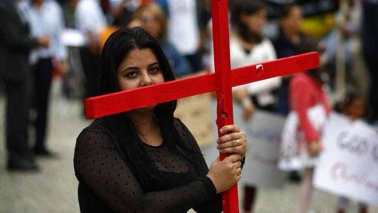 Een vrouw draagt een kruis tijdens een demonstratie van Iraakse christenen tegen de onderdrukking van de Islamitische Staat. Beeld reuters
