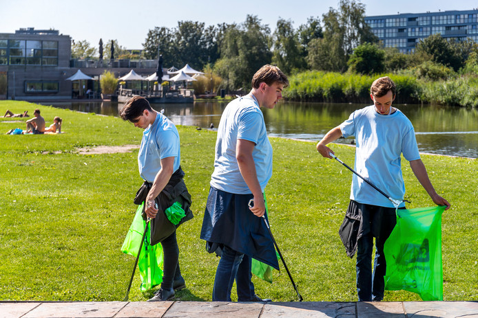 Gekleed in lichtblauwe T-shirts en voorzien van vuilniszak en grijper ruimen de studenten in het Griftpark rommel op.