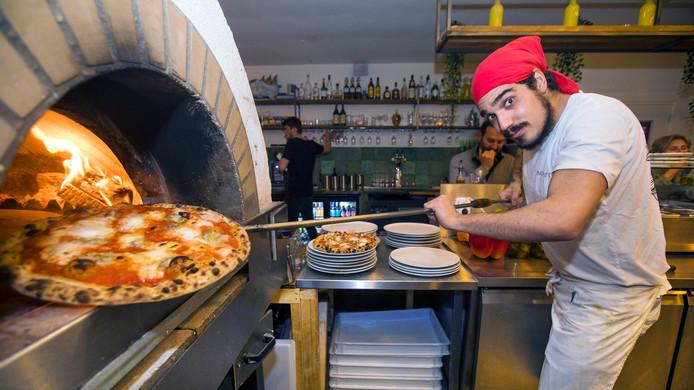 Pizzabakker Andrea haalt een pizza quattro formaggi uit de oven.