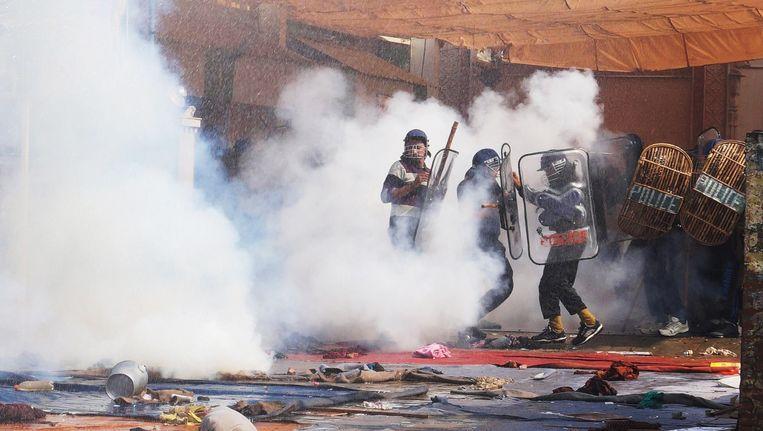 Agenten gaan de aanhangers van de goeroe met traangas te lijf.