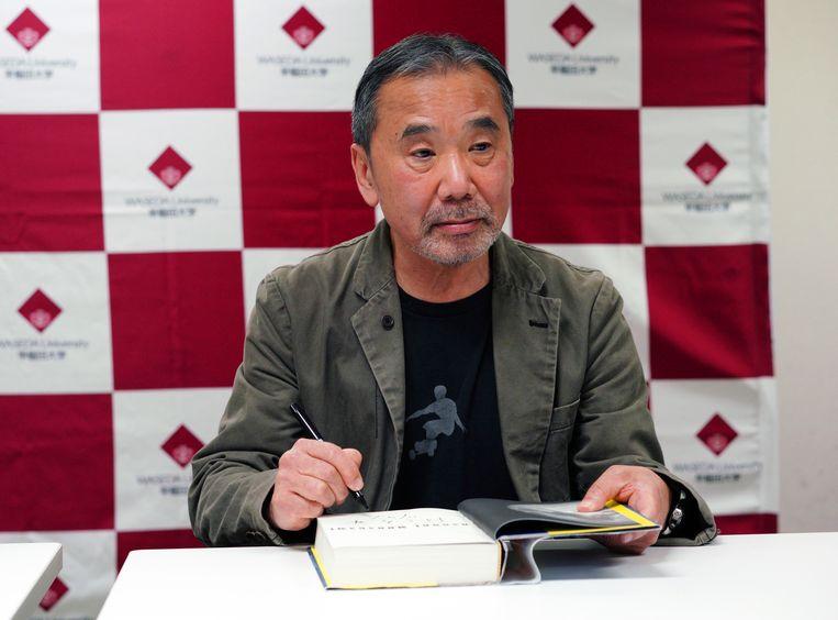 De Japanse schrijver Haruki Murakami signeert een boek tijdens de persconferentie.