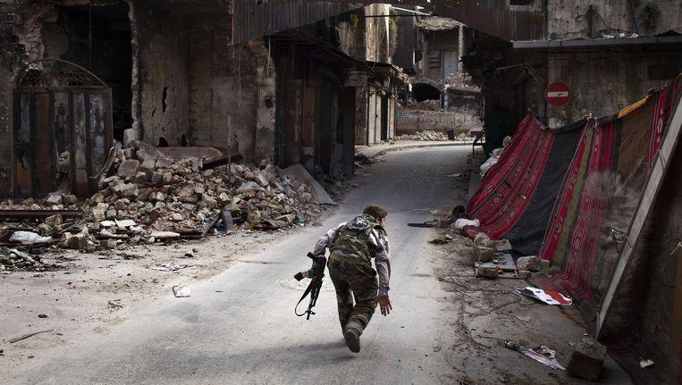 Een strijder steekt de straat over in Aleppo en probeert sluipschutters te ontwijken. Beeld AFP