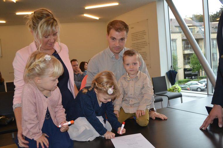 De drie kindjes plaatsen hun handtekening op huwelijksakte van hun ouders.
