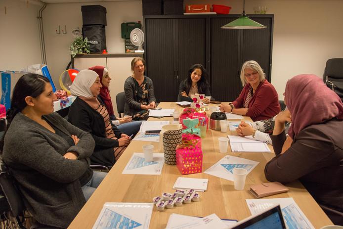 Allochtone moeders bespreken opvoedingskwesties met medewerkers van Buurtzorg Jong in ontmoetingscentrum Stroud.