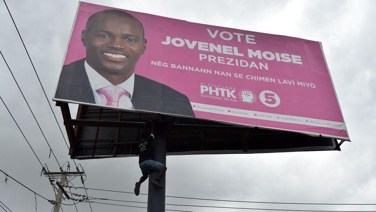 Een demonstrant in Port-au-Prince klimt in een paal met een poster van presidentskandidaat Jovenel Moise. Beeld anp