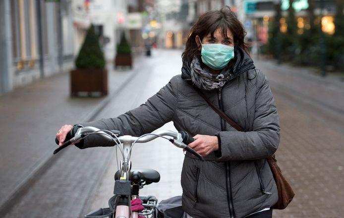 Een vrouw met mondkapje, in een vanwege asbest afgesloten Roermond.