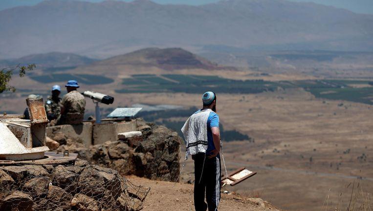 Een man kijkt naar Syrië vanuit een door VN-vredessoldaten bewaakte legerpost op de Bentalberg in het Golanhoogte-gebied. Beeld AFP