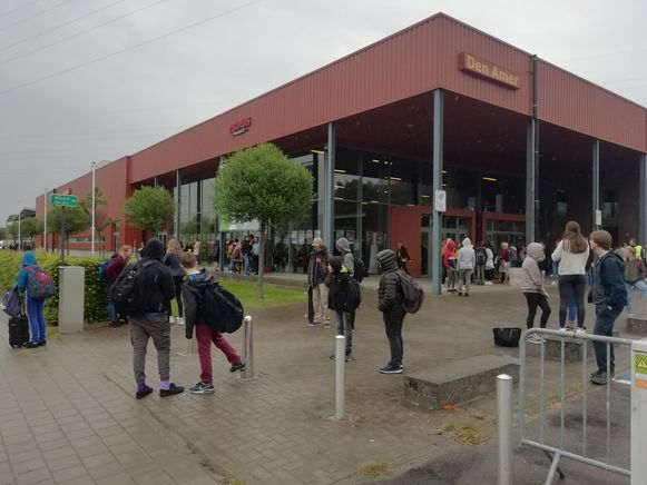 Leerlingen wachten bij Den Amer om te worden opgehaald door hun ouders.