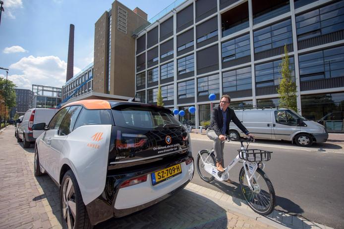 Boudie Hoogedeure bij gebouw TQ op Strijp-T in  Eindhoven met een Hopper-leenfiets, bij een van de elektrische deelauto's van Amber die hier binnenkort ook te vinden zijn.