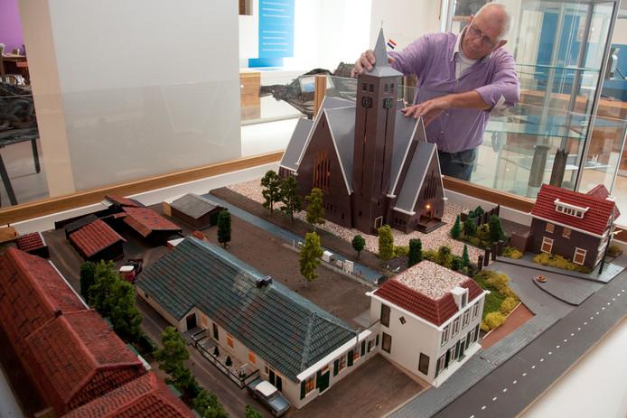 Henk van Voskuilen bezig met een schaalmodel van de Julianakerk in Veenendaal.