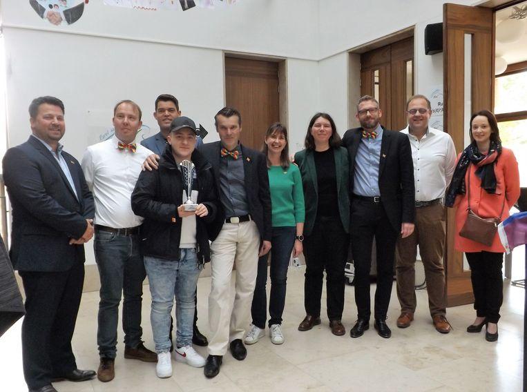 Het gemeentebestuur en een aantal leden van Regenboog Niel nemen de trofee voor 'holebivriendelijkste gemeente' in ontvangst.