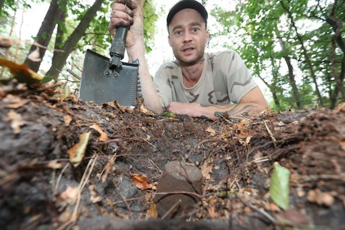 De vrijwilliger bij de op scherp staande brisantgranaat die hij vond in het bos in Arnhem.