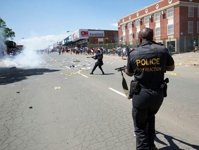 De politie probeert de menigte onder controle te houden tijdens de rechtszaak tegen de vermoedelijke kannibalen in Escourt.