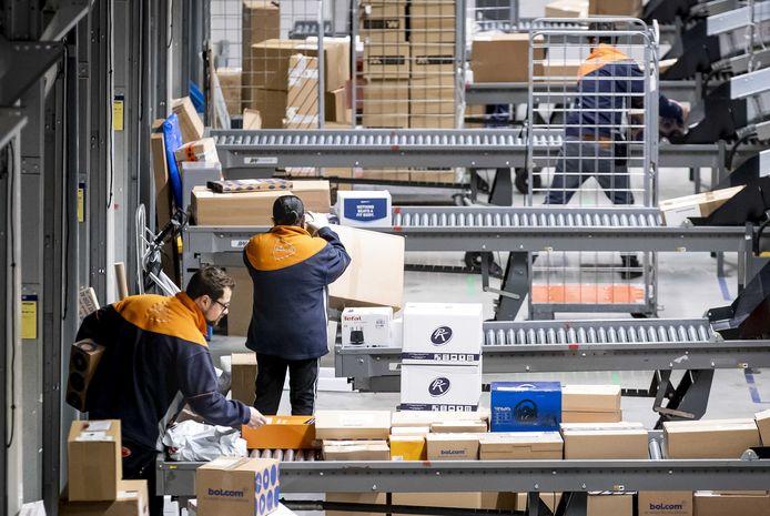 Medewerkers van post- en pakketbezorger PostNL sorteren in aanloop naar Black Friday pakketjes in het pakkettensorteercentrum.