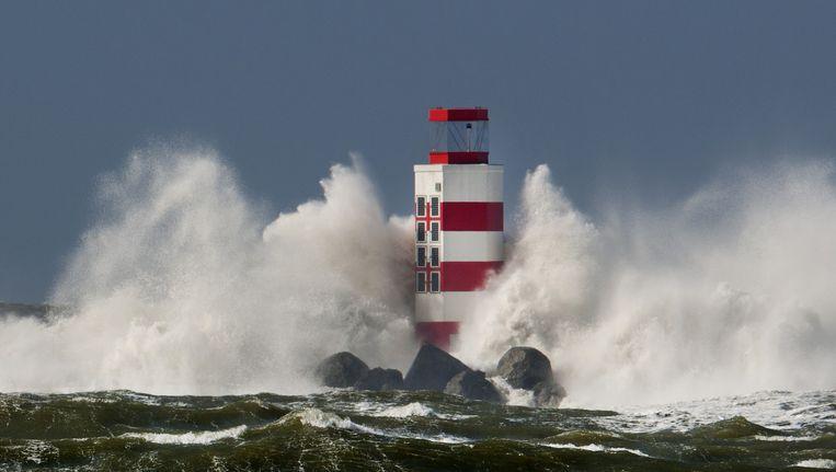 Hoge golven slaan tegen de vuurtoren aan het eind van de Noordpier bij IJmuiden tijdens de storm. Beeld anp