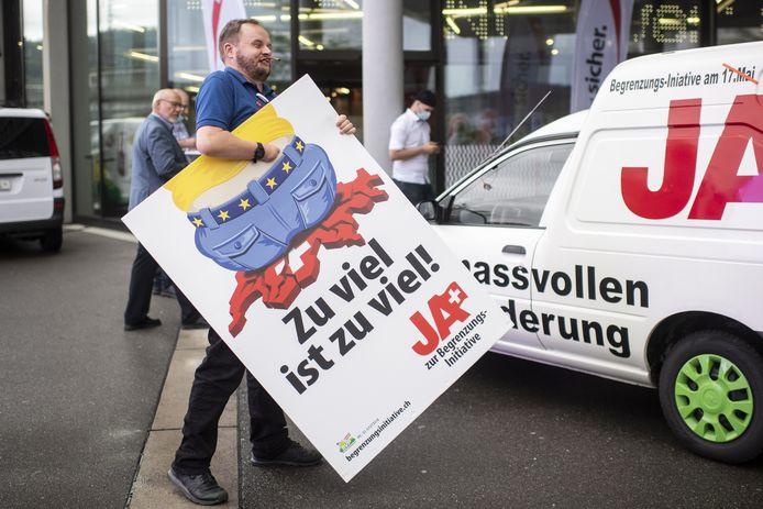 Een man is in de weer met een poster van de SVP: 'Te veel is te veel'.