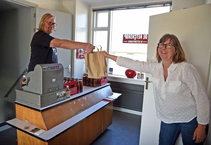 Patrick Keizer demonstreert hoe hij veilig een tasje met ketchup overhandigt aan een klant, in dit geval zijn partner Lineke.