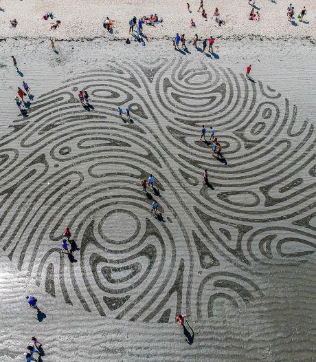 Il crée de gigantesques gravures géométriques dans le sable qui ne durent que quelques heures