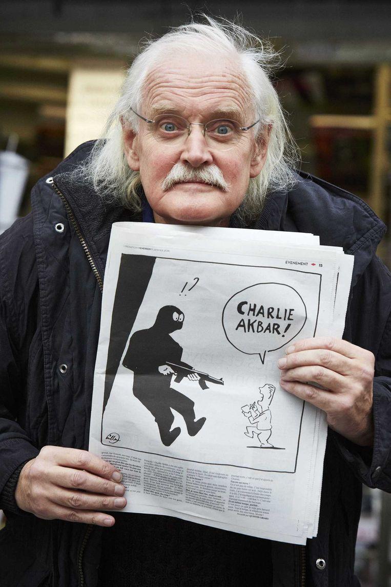 Bernard 'Willem' Holtrop poseert met de tekening die hij maakte voor Libération. Beeld Pierre Crom / ANP
