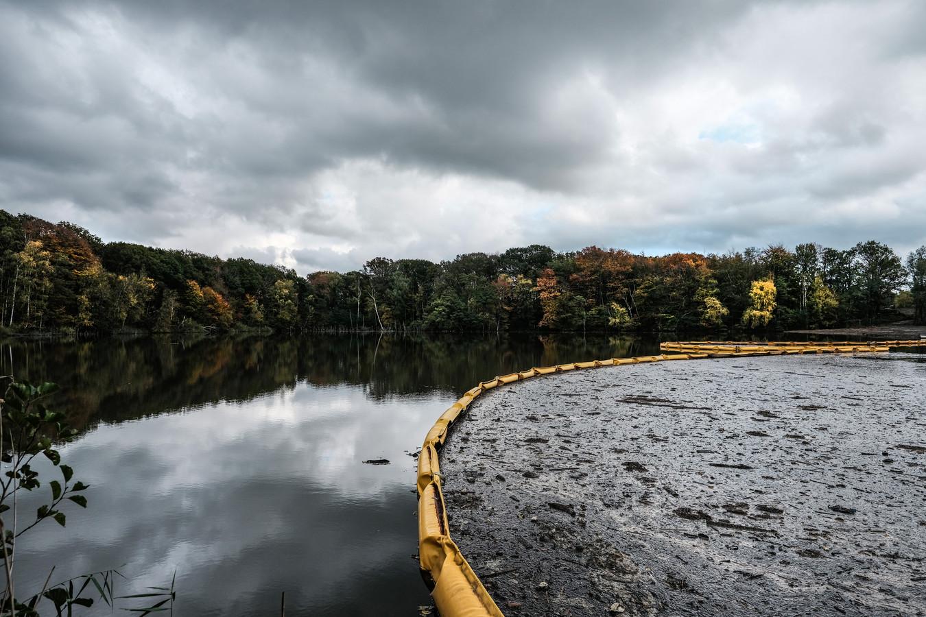 Het drijvende afval uit de stortingen in de kleiput hoopt zich op tegen een gele drijfband. Jan van den Brink