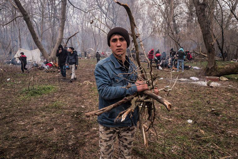 Vluchtelingen rapen takken bij elkaar voor kampvuurtjes. Beeld Nicola Zolin