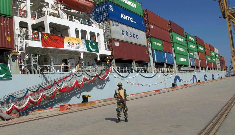 Een Pakistaanse marinier bewaakt een volgeladen Chinees schip dat op het punt staat de haven van de Pakistaanse stad Gwadar te verlaten. Beeld AP