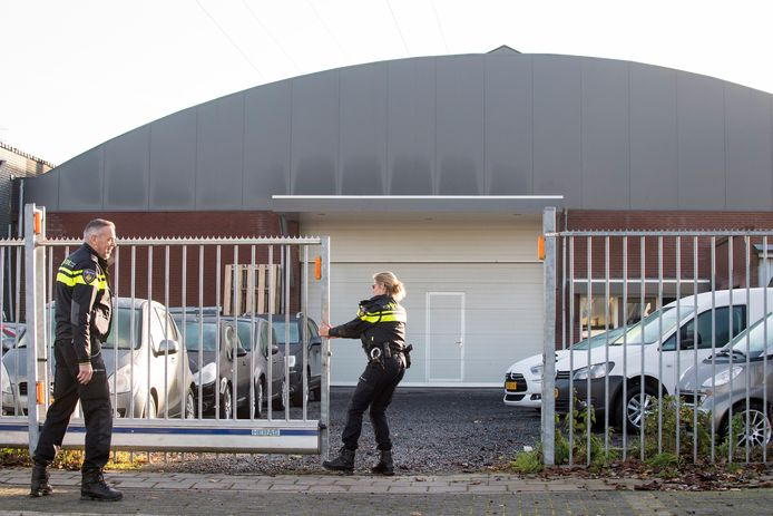Een agent sluit de poort weer van het Tielse bedrijf waar de politie binnenviel.