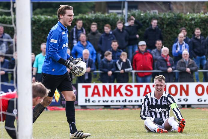 Doelman Desny Royendijk (met bal) van Achilles'29 roept zijn verdediging tot de orde in de derby tegen De Treffers. Rechts aanvoerder Jesse Edge.