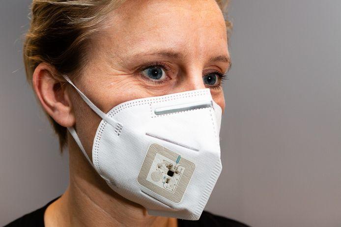Een vrouw met een prototype van het masker dat werd ontwikkeld met sensoren die wasbaar en plooibaar zijn.