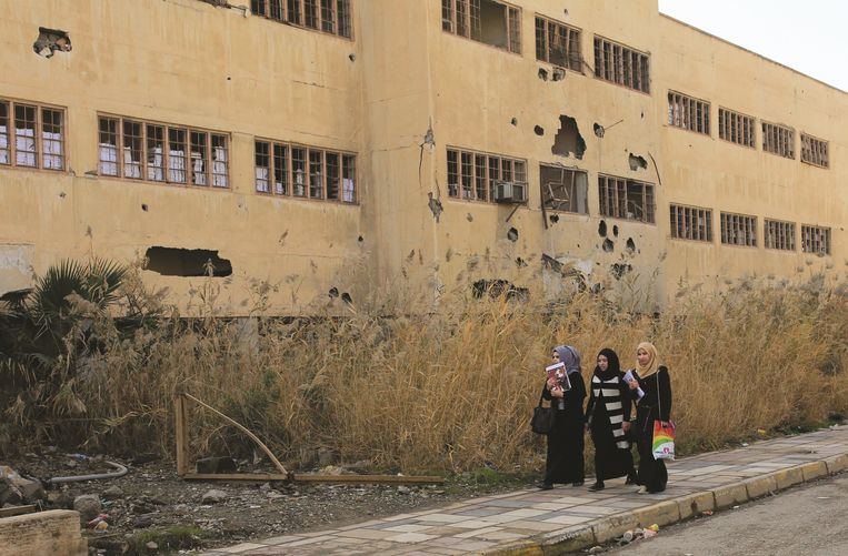 De inwoners van Mosul hebben het dagelijks leven weer opgepikt. Hier lopen drie studentes langs de universiteit van Mosul. Beeld Getty Images