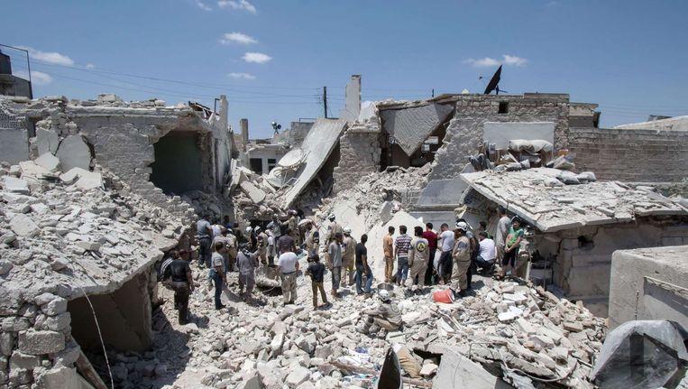 Reddingswerkers tussen verwoeste gebouwen in Aleppo op 21 juni Beeld afp