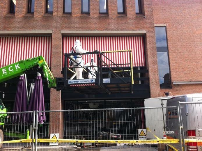 Mannen in witte pakken op weg naar het dak van het theater om asbest te verwijderen. Foto Paul Roovers/BD