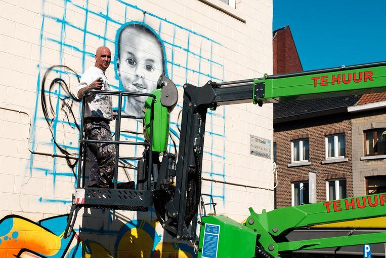Graffiti-artiest Cesa tijdens het maken van de muurschildering  voor  Kenric.