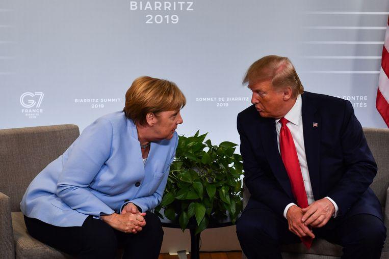 Trump (rechts) met de Duitse bondskanselier Angela Merkel (links) bij de G7-top in het Franse Biarritz, in 2017. Beeld AFP