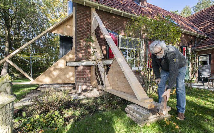 Kees van der Werf tikt een houten wig aan, in de constructie waarmee een hoek wordt gestut van het in 1952 gebouwde voorhuis van de boerderij.