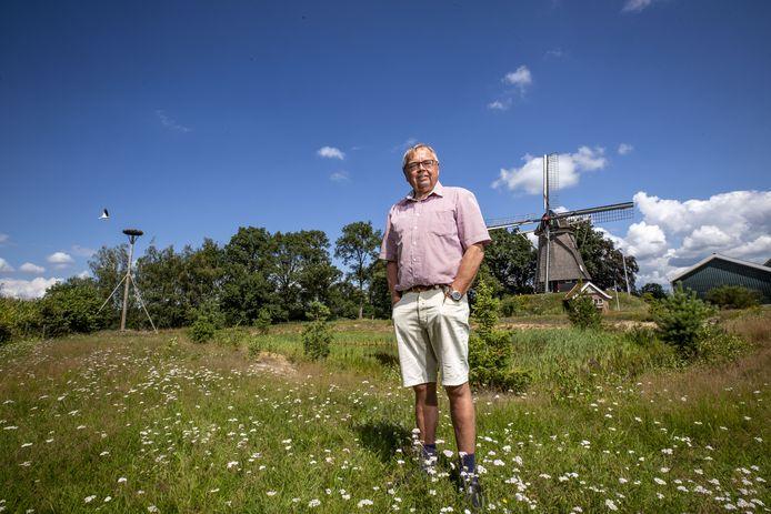 Jos Brunninkhuis in de wei naast zijn woning aan de Frensdorferweg in Tilligte. Achter hem de Westerveldmolen en daarnaast het nieuwe ooievaarsnest waar net de laatste vogel even weg vliegt.