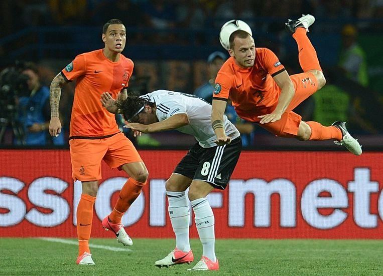 Van der Wiel (links) en Heitinga torpederen de Duitse speler Özil. Beeld afp