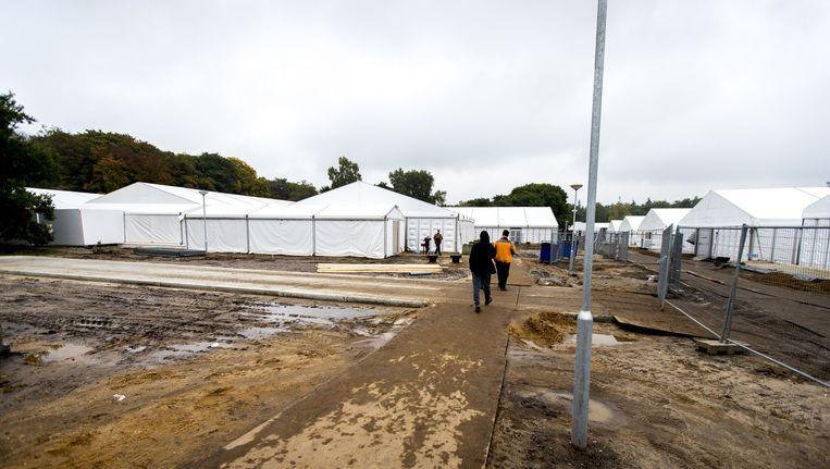 Asielzoekers lopen over het terrein met het tentenkamp dat dient als tijdelijke noodopvanglocatie voor 3000 vluchtelingen op het ruim 600 hectare tellende Heumensoord bij Nijmegen. Beeld anp