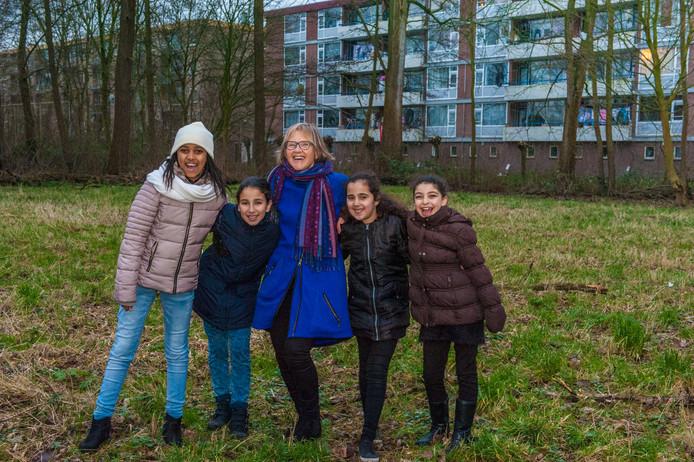 Juf Loes Ostendorf en enkele kinderen uit Gouda-Oost op de plek waar tot hun vreugde binnenkort een natuurspeelplaats wordt aangelegd.