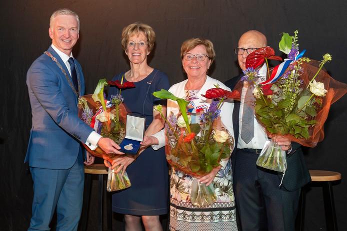Voorzitter Pauline den Hartog, secretaris Nel Kortman en penningmeester Ton Poots krijgen de erepenning uit handen van burgemeester Robert Strijk.