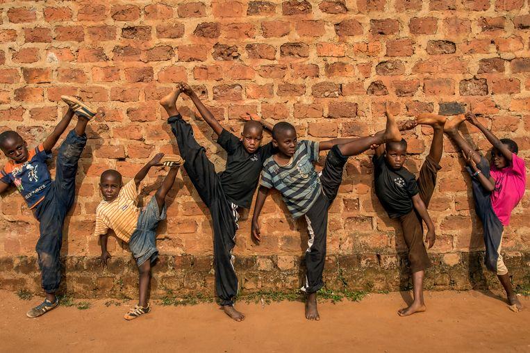 Een groep kinderen oefent kungfu in Kampala, Oeganda.  Beeld Frederic Noy