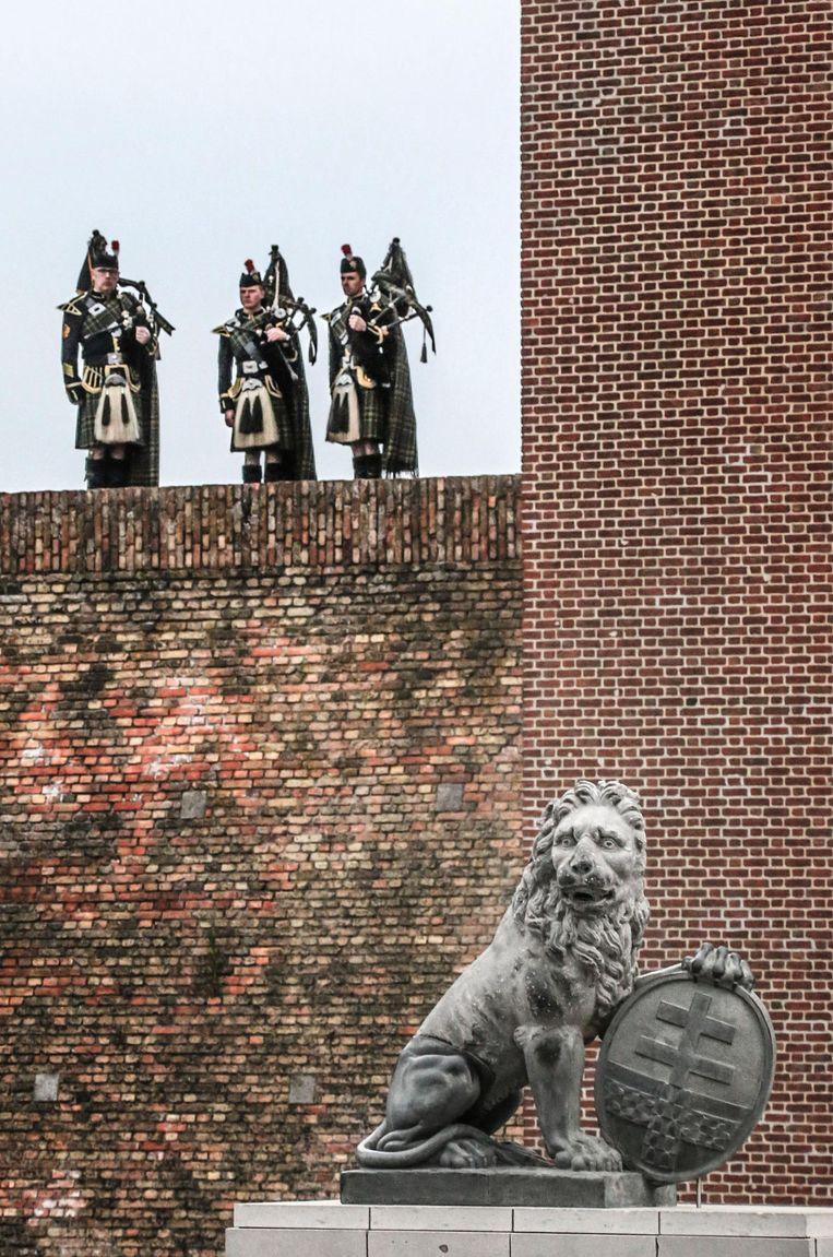 Doedelzakspelers kijken uit over Ieper terwijl een van de twee leeuwen zijn plek weer opeist.