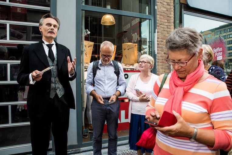 Terwijl een acteur Leon Splliaert neerzet (links) volgen de deelnemers het verhaal op hun smartphone.