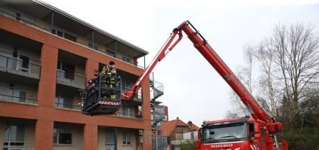 Lift stuk, brandweer helpt vrouw in rolstoel naar boven met hoogwerker