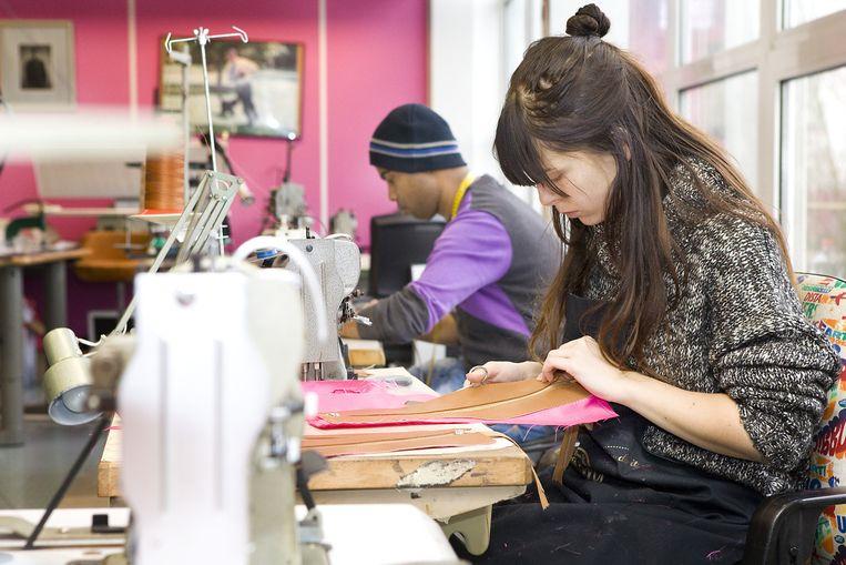 d93266ebc15 Medewerkers van Omar Munie in zijn atelier in Den Haag, waar de tassen met  de hand worden gemaakt. Beeld Io Cooman