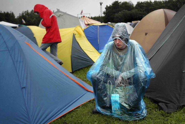 Een festivalbezoeker tijdens een regenachtige dag op Lowlands in 2004.  Beeld de Volkskrant / Marcel van den Bergh