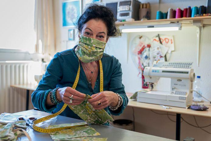 Lucia Schols, een van de vrijwilligers van VEADS die mondkapjes maken voor onder meer zorginstellingen. Deskundigen raden het juist af om zelf mondmaskers te maken.