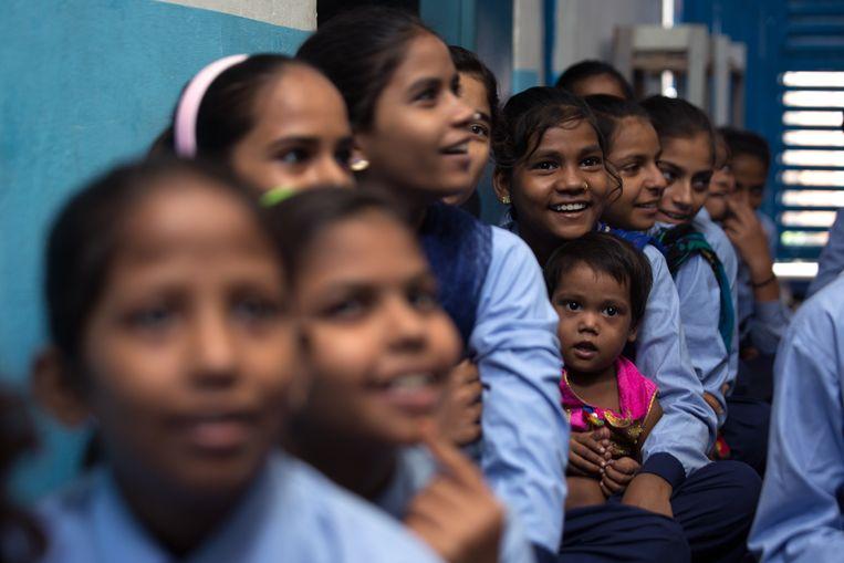 Mahinoor (12) op school, met haar kleine zusje op haar arm.  Beeld Ruhani Kaur