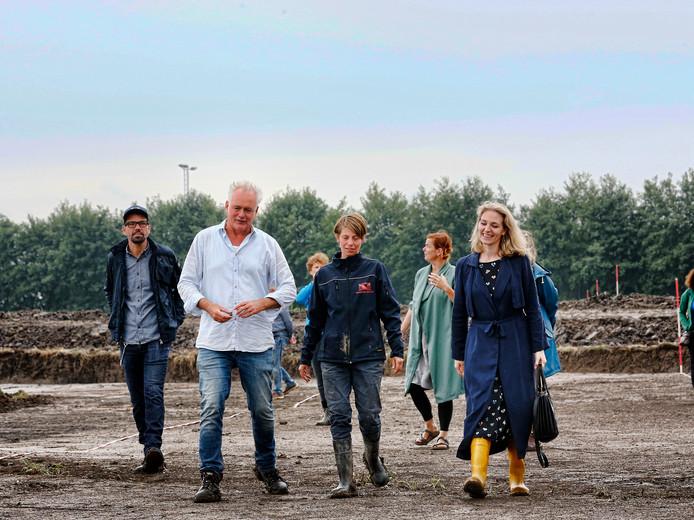 Archeoloog Herre Wynia leidt o.a. wethouder Anke Klein (gele laarsjes) over de opgegraven weg.