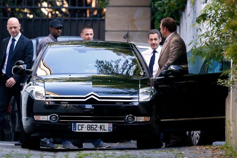 Nicolas Sarkozy verlaat zijn woning in Parijs. Beeld reuters